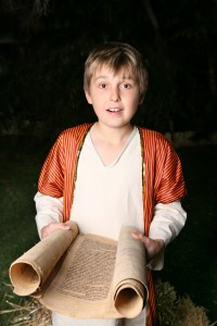 Boy reading from a gevil parchment scroll.  This one is written on goat skin.