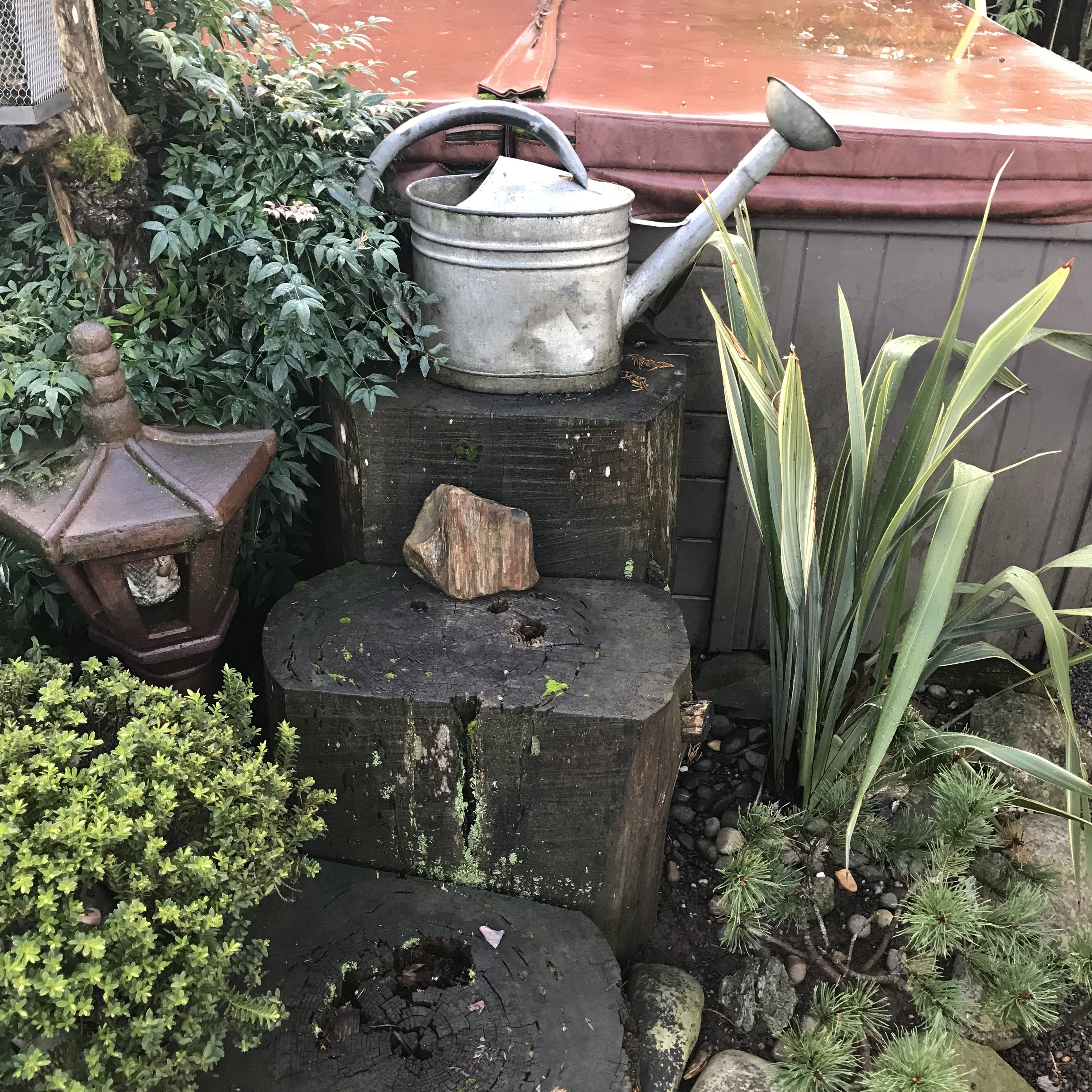 Watering can on log steps in landscaping